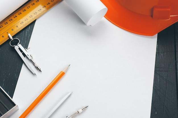 Miejsce pracy inżyniera z planami, kompasem, ołówkiem i hełmem ochronnym