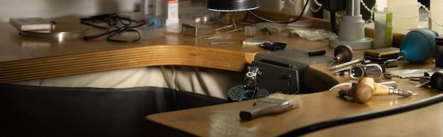 Miejsce pracy jubilera. szerokie ujęcie panoramiczne. widok z boku stołu warsztatowego jubilera z różnymi narzędziami na drewnianym stole. tło koncepcji złotnika