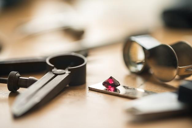 Miejsce pracy jubilera. widok z boku stołu warsztatowego jubilera z różnymi narzędziami i rubinem na drewnianym stole. tło koncepcji złotnika