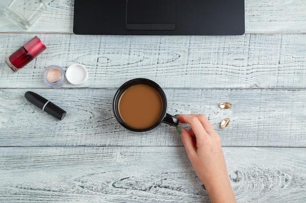 Miejsce pracy kobiety z laptopem, filiżanką kawy i kosmetykami