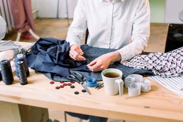 Miejsce pracy krawcowej. przytnij obraz krawcowych rąk szyjących guzik. guziki, materiały do spodni, wzór, nożyczki, nici i igły, taśma miernicza i filiżanka herbaty na stole.