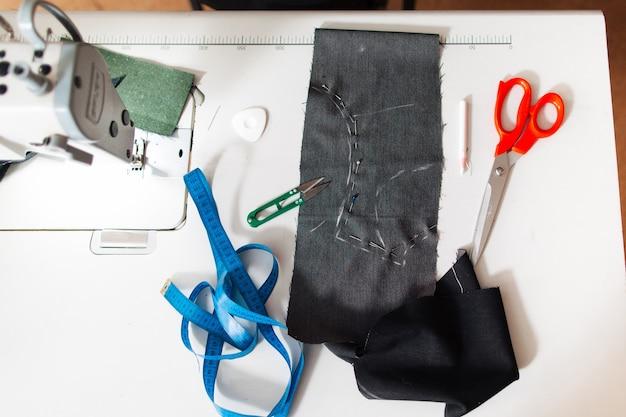 Miejsce pracy krawcowej z tkaniny i narzędzi na biurku