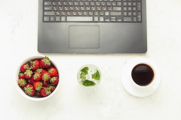 Miejsce pracy. laptop, w misce truskawek, orzeźwiający napój z lodem i miętą, filiżanka kawy. widok z góry, leżał płasko.