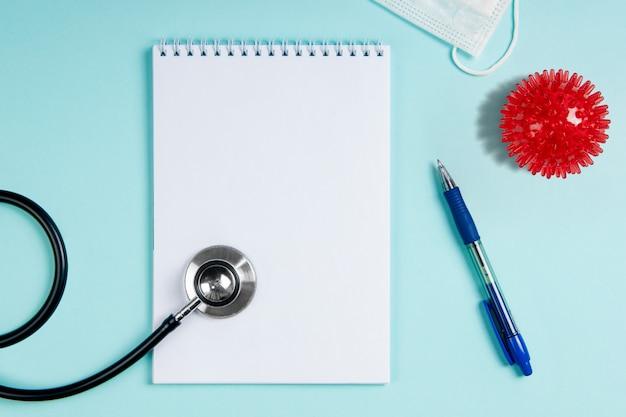 Miejsce pracy lekarza flatlay z maską i makietą notatnika. nowa koncepcja koronawirusa 2019-ncov. epidemia chińskiego koronawirusa