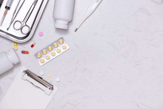 Miejsce pracy lekarza. stetoskop, schowek, pigułki i inne rzeczy na biurku.