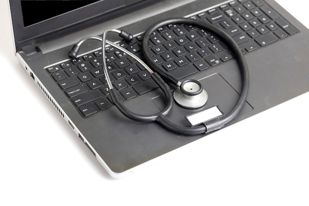 Miejsce pracy lekarza z laptopem i stetoskopem na białym tle