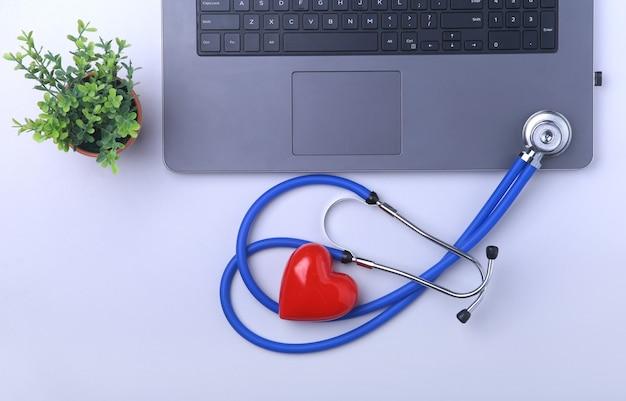 Miejsce pracy lekarza z laptopem, stetoskopem, receptą rx, okularami i czerwonym sercem i notebookiem na białym stole. widok z góry. skopiuj miejsce.