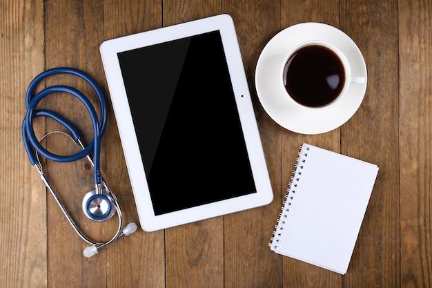 Miejsce pracy lekarza z pustą tabletką i stetoskopem na drewnianej powierzchni