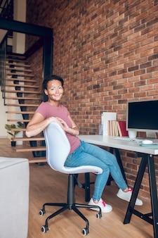 Miejsce pracy. młoda afroamerykanka siedzi przy stole w swoim miejscu pracy