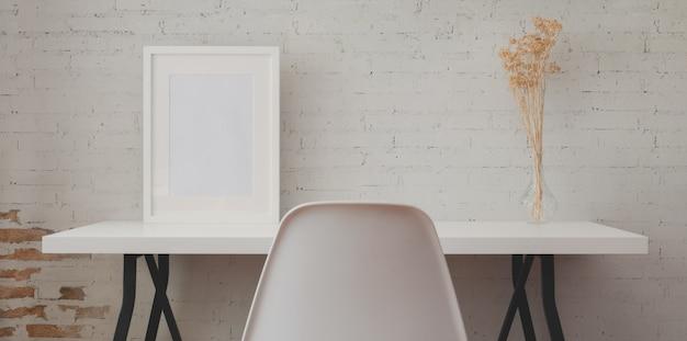 Miejsce pracy na poddaszu z białym drewnianym biurkiem, ramą makiety i wazonem w vintage ceglanym murze