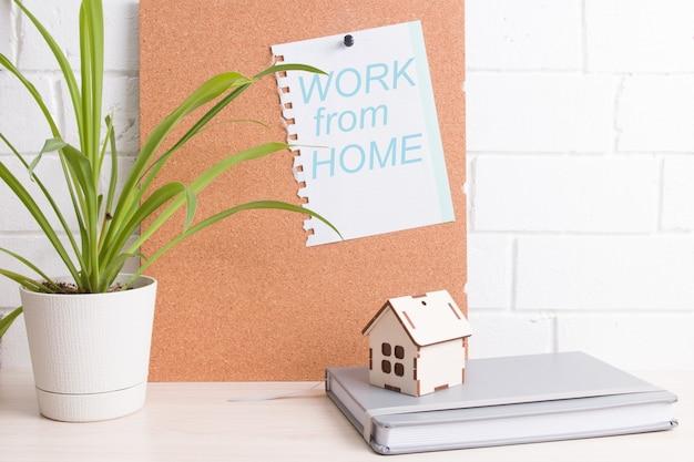 Miejsce pracy na samoizolacji, tablica korkowa, kwiatek i notatnik w tle