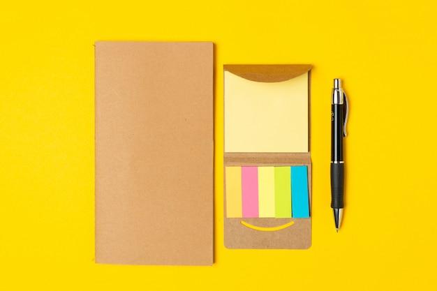 Miejsce pracy, notatnik, karteczki i długopis na jasnożółtym kolorze