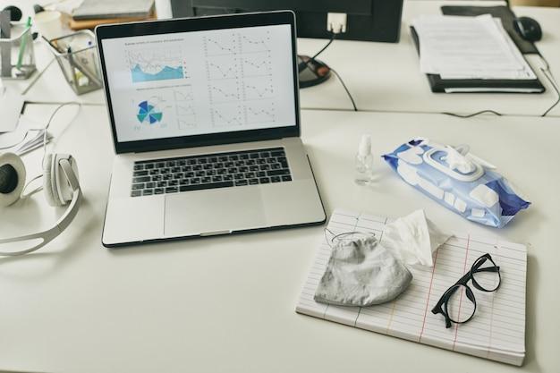 Miejsce pracy nowoczesnego brokera z wykresem finansowym i schematem na wyświetlaczu laptopa w otoczeniu środka dezynfekującego, maski, okularów i chusteczek antyseptycznych