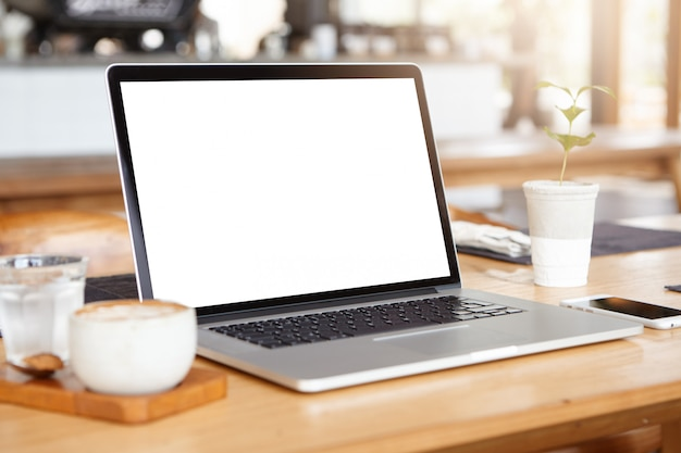 Miejsce pracy osoby samozatrudnionej: typowy laptop pc spoczywający na drewnianym stole ze smartfonem, kubek kawy i szklanka wody.