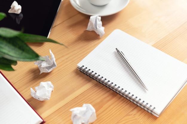 Miejsce pracy pisarza z notatnikiem i długopisem. zmięte papiery, przezroczysty arkusz w zeszycie na drewnianym stole