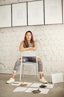 Miejsce pracy projektanta mody. jasne, słoneczne studio z kobietą kreatywną patrząc na kamery.