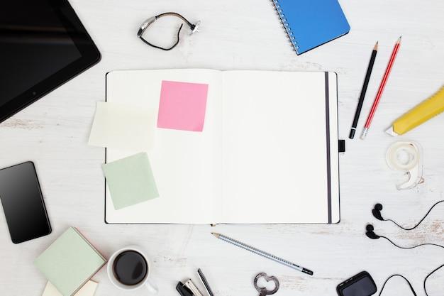 Miejsce pracy pusty notatnik tablet pc i inteligentny telefon na białym drewnianym stole