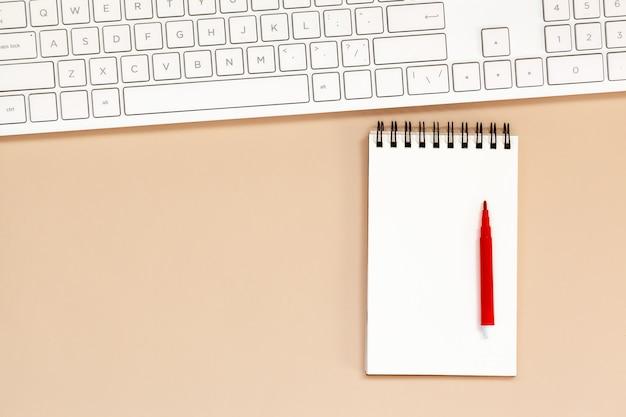 Miejsce pracy pusty spiralny notatnik z klawiaturą na stole.