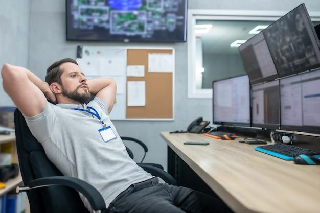 Miejsce pracy, rozgrzewka. zmęczony uważny mężczyzna w szarym tshirt z odznaką siedzi patrząc na monitory przy pracy