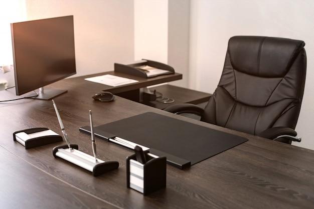 Miejsce pracy szefa firmy: skórzane krzesło, przybory do pisania, monitor.