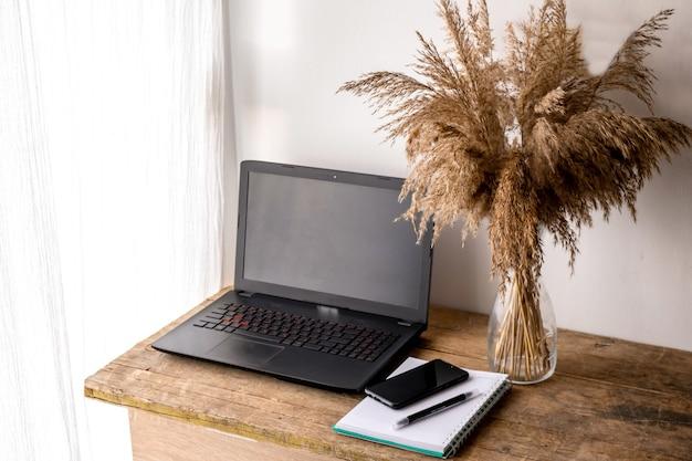 Miejsce pracy w biurze domowym z drewnianym biurkiem. widok z góry na klawiaturę z notatnikiem, długopisem, smartfonem, pampasami. przestrzeń do nowoczesnej pracy twórczej projektanta. koncepcja biznesu i finansów.