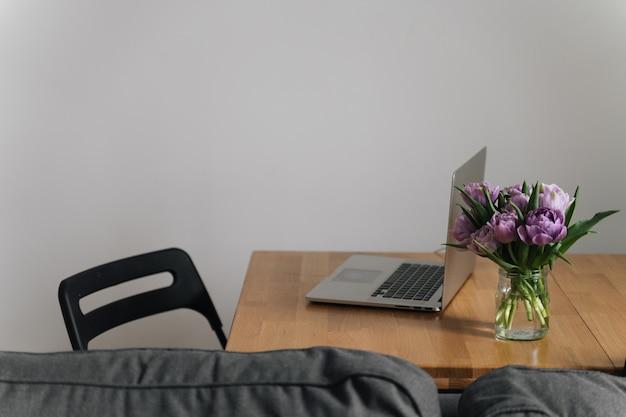 Miejsce pracy w biurze domowym z laptopem i kwiatami tulipanów. 8 marca. wiosna. powolne życie. świadomy