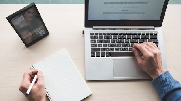 Miejsce pracy w biurze mężczyzna pracujący na laptopie przed oknem