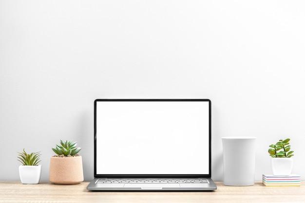 Miejsce pracy w biurze, w domu z laptopem, filiżanką i roślinami na stole, miejsce na kopię.