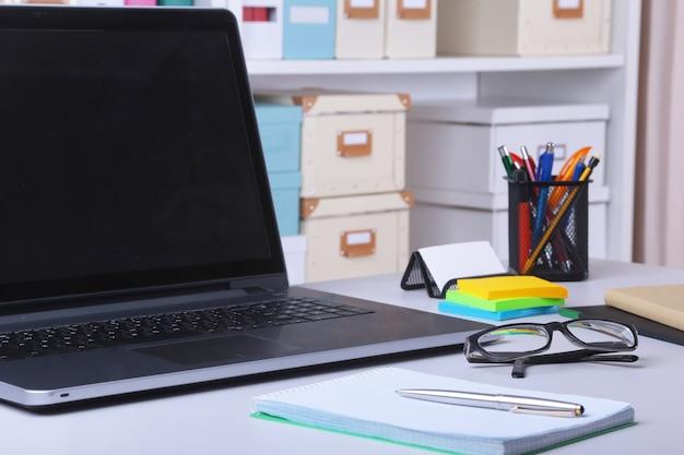 Miejsce pracy w biurze z laptopem, myszą, notatnikiem, okularami, piórem.