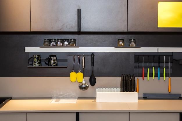 Miejsce pracy w kuchni z wielokolorowymi nożami, szklanymi talerzami i półką z przyprawami
