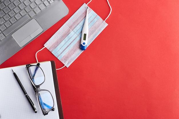 Miejsce pracy w kwarantannie. domowe miejsce pracy. praca zdalna z domu. pusty biały papier i czarny długopis, maska medyczna, termometr, słuchawki i laptop