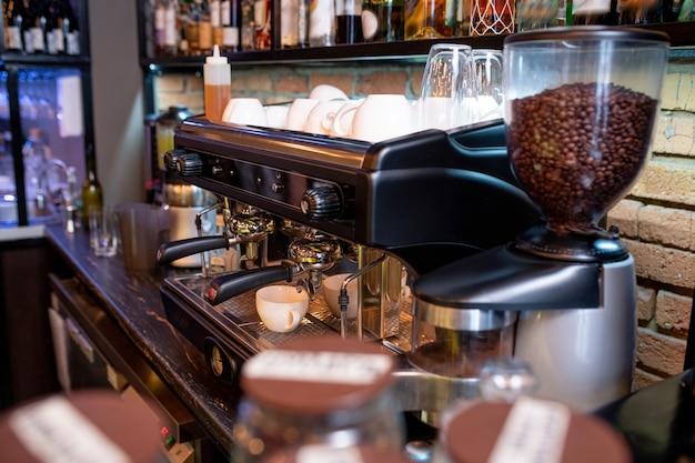 Miejsce pracy współczesnego baristy z ekspresem do kawy, czystymi filiżankami i szklankami oraz butelkami z alkoholem na półce powyżej