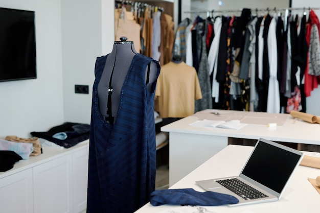 Miejsce pracy współczesnej szwaczki lub krawca z niedokończoną częścią garderoby na manekinie, laptopie i kawałku materiału na biurku