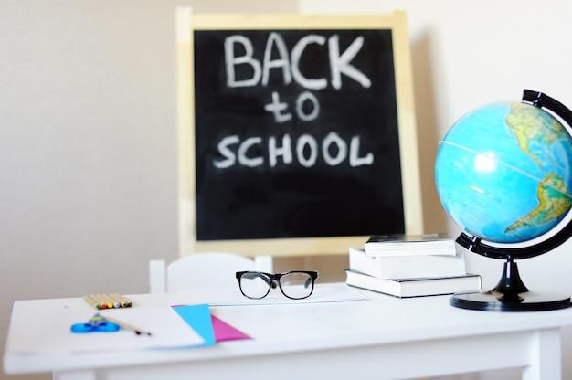 Miejsce pracy z biurkiem szkolnym, tablicą, globusem i okularami.
