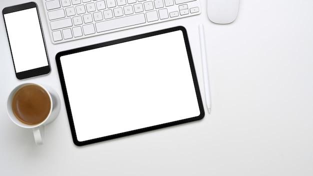 Miejsce pracy z cyfrowym tabletem, smartfonem, klawiaturą i filiżanką kawy na białym biurku.