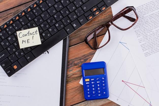 Miejsce pracy z dokumentem okularów na klawiaturę i niebieskim kalkulatorem
