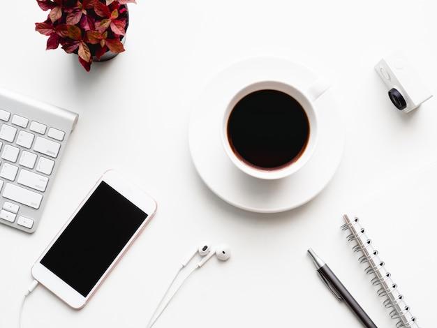 Miejsce pracy z filiżanką kawy, notatnikiem, smartfonem.