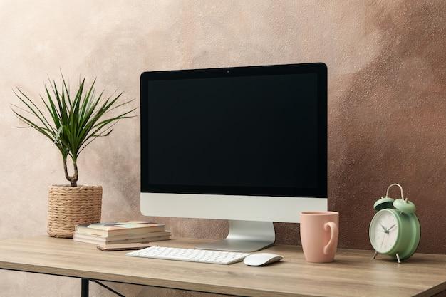 Miejsce pracy z komputerem i rośliną na drewnianym stole. jasnobrązowy