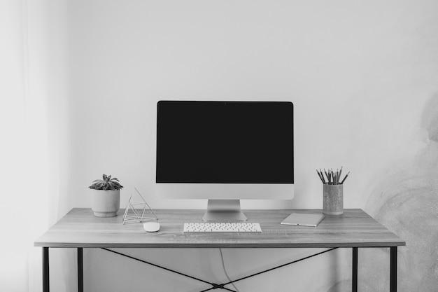 Miejsce pracy z komputerem, pastylką i rośliną na drewno stole, przestrzeń dla teksta