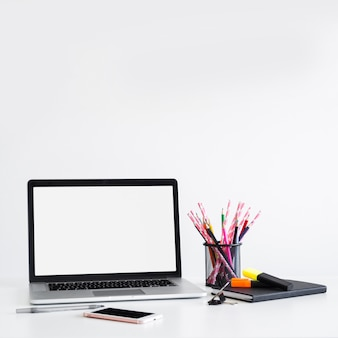 Miejsce pracy z laptopem blisko pióra, ołówki wewnątrz może i smartphone