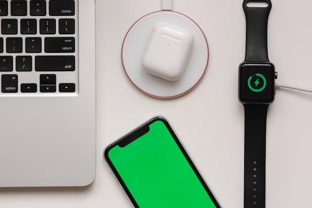 Miejsce pracy z laptopem na stole i urządzeniach. bezprzewodowe ładowanie inteligentnego zegarka i słuchawek bezprzewodowych na białym stole. smartfon z zielonym ekranem, makiety. widok z góry.