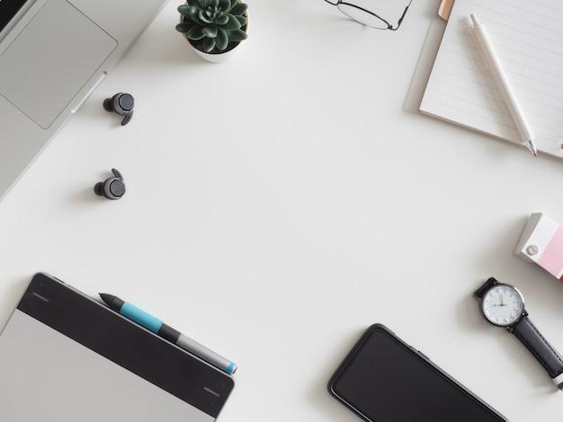 Miejsce pracy z laptopem, notatnikiem, tabletem graficznym i smartfonem.