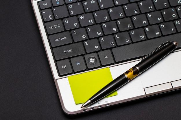 Miejsce pracy z notatnikiem i laptopem na czarno.