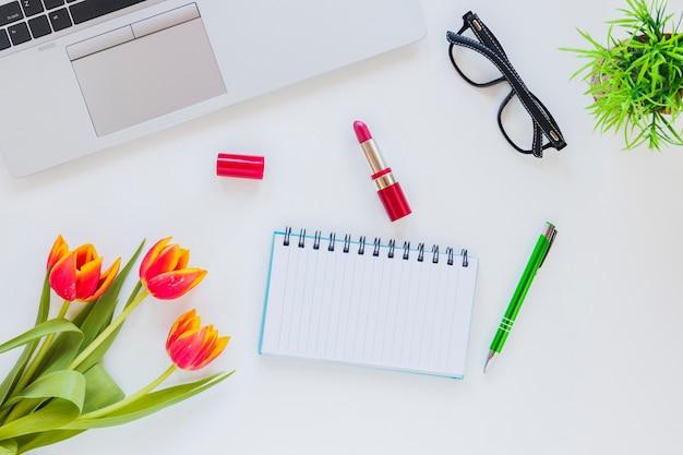 Miejsce pracy z notatnikiem i laptopem z tulipanem i pomadą