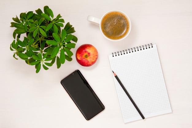 Miejsce pracy z notatnikiem, telefonem, ołówkiem, filiżanką kawy i kwiatkiem doniczkowym jest umieszczone na białym tle. płaska łyżka, widok z góry.