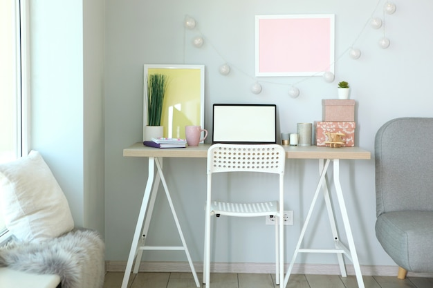 Miejsce pracy z nowoczesnym laptopem we wnętrzu pokoju