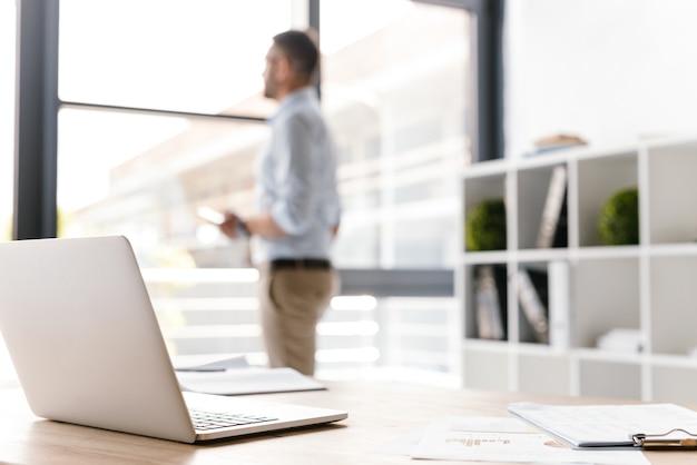 Miejsce pracy z otwartym białym laptopem leżącym na stole, podczas gdy niewyraźny biznesmen stoi i patrząc przez duże okno