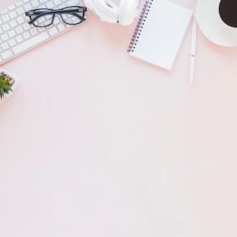 Miejsce pracy z różnorodnymi gadżetami notatnik i filiżanka kawy na różowym tle