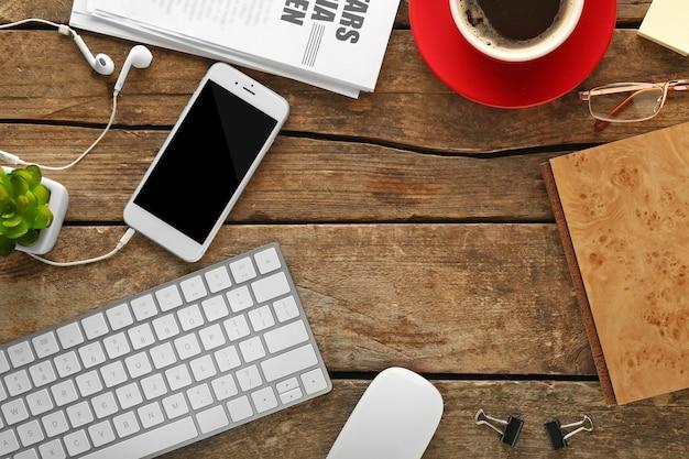 Miejsce pracy z telefonem komórkowym, urządzeniami peryferyjnymi i gazetą na drewnianym stole