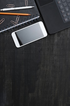 Miejsce pracy ze smartfonem, notatnikiem, na czarny stół. widok z góry